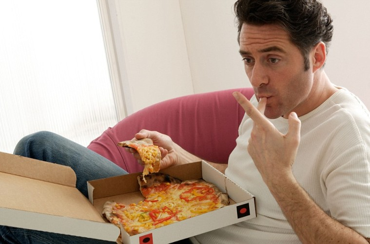 AT39BX A man sitting in front of a TV eating pizza